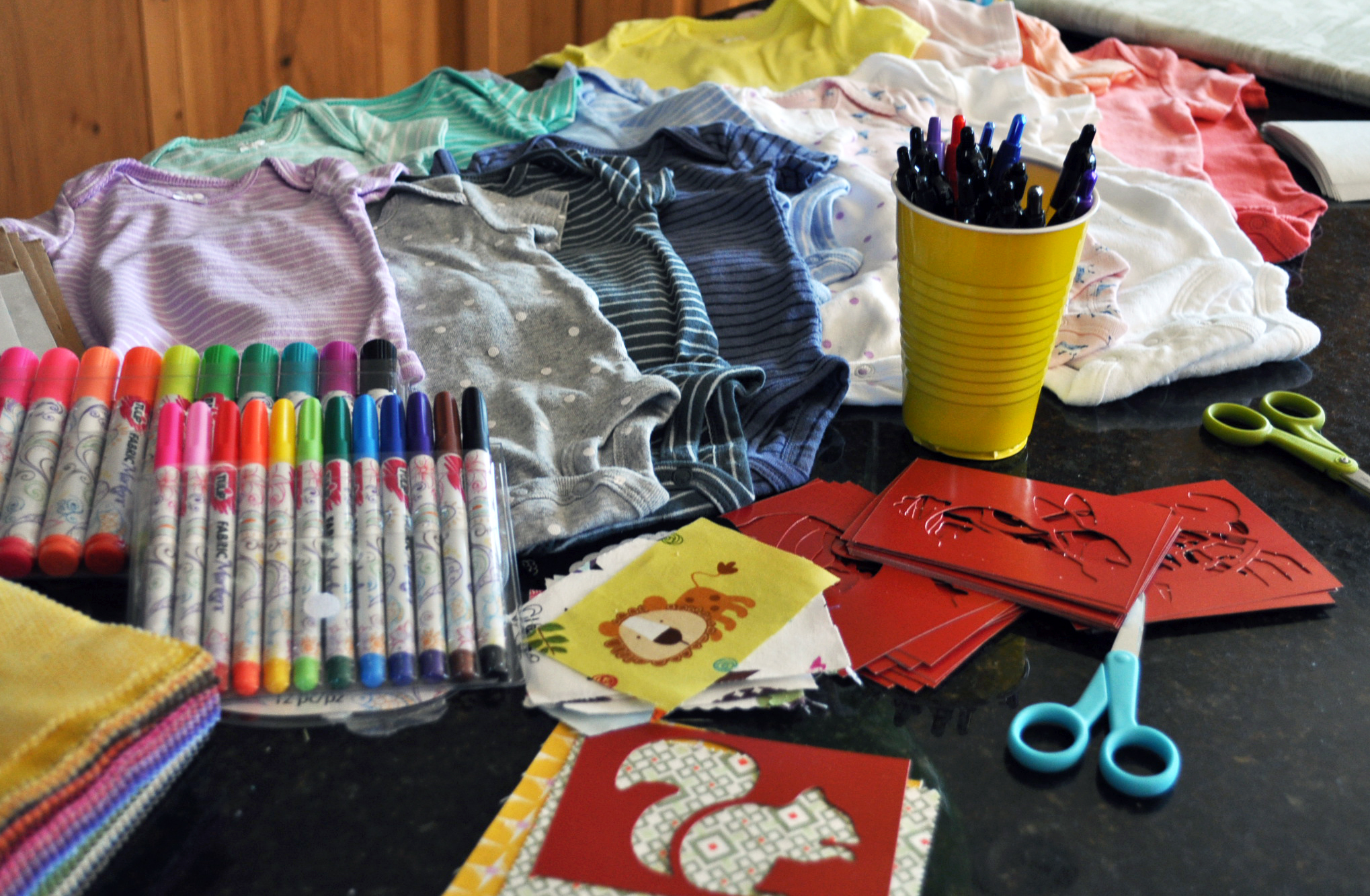 Onesie decorating station set up on the kitchen island- stencils, markers, fabric and fusible!